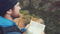 man holding a map in the wilderness