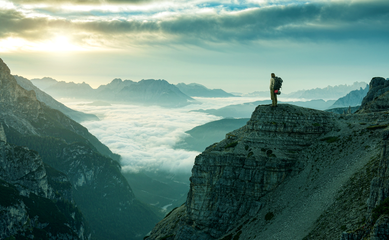 hiker-standing-on-the-edge-of-a-mountain