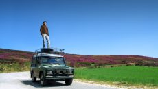 man-standing-on-car-adventure
