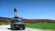 man-standing-on-car-adventure
