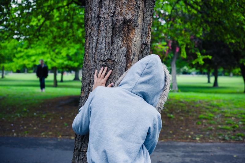 person-hiding-behind-tree