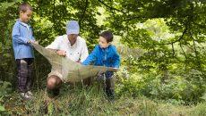 father teaching children in the wild