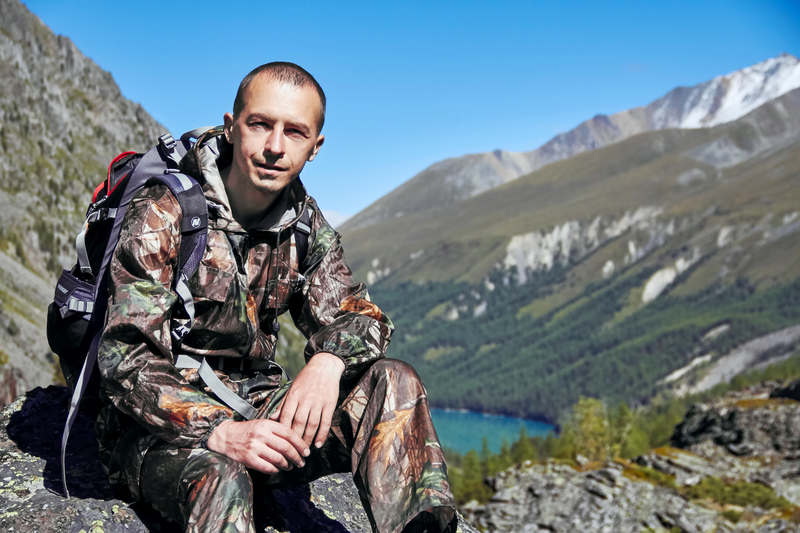 man in camo resting on a mountain
